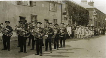 New Buckenham Band on parade.  Note George and Dragon carving on corner of pub